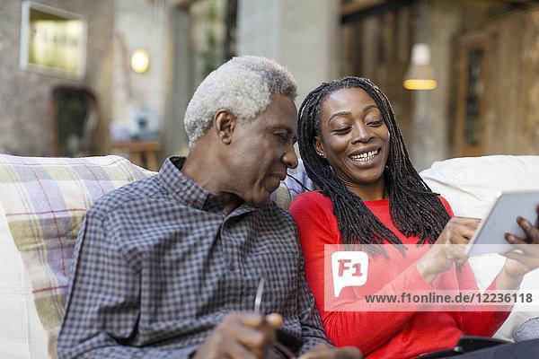 Adult Tochter zeigt Senior Vater  wie man digitale Tabletten benutzt.