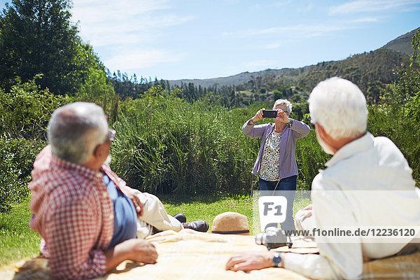 Aktive Seniorin mit Fotohandy beim Fotografieren von Männern  die sich auf einer sonnigen Picknickdecke entspannen.