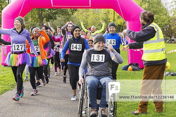 Mann im Rollstuhl und Läufer erhalten Medaillen  überqueren die Ziellinie des Charity-Rennens