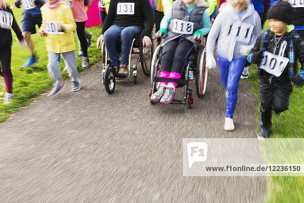 Menschen im Rollstuhl und Läufer  die sich beim Benefizlauf bewegen