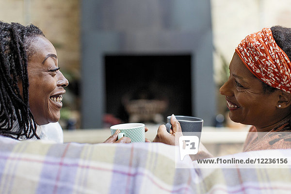 Smiling women friends talking and drinking tea on sofa