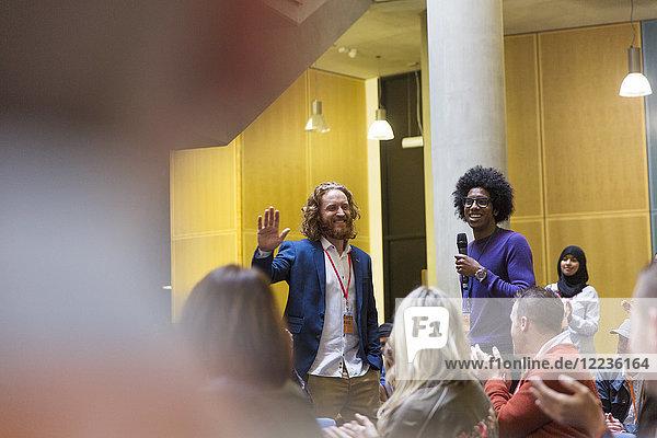 Konferenzpublikum klatscht für männliche Referenten