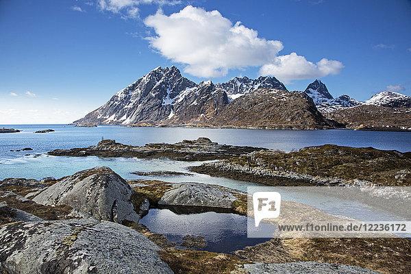 Felsiges Gebirge unter blauem Winterhimmel über Fjord  Sund  Flakstadoya  Lofoten  Norwegen