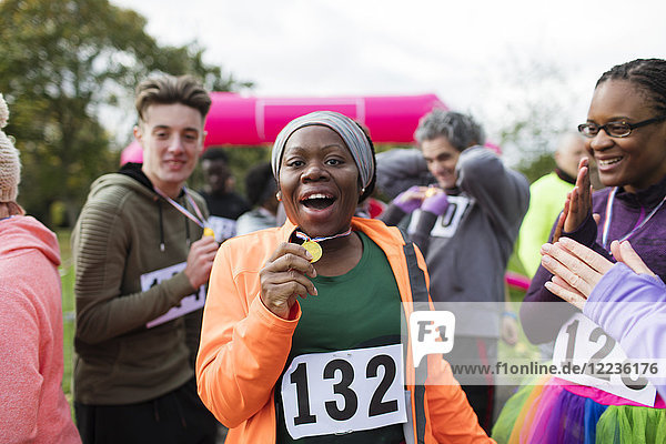Portrait begeisterte Läuferin mit Medaille beim Benefizlauf