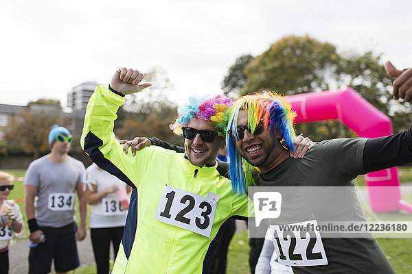 Portrait verspielte männliche Läufer mit Perücken und jubelndem Charity-Lauf im Park
