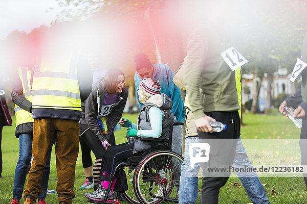 Frau im Rollstuhl im Gespräch mit Freunden beim Charity-Rennen im Park