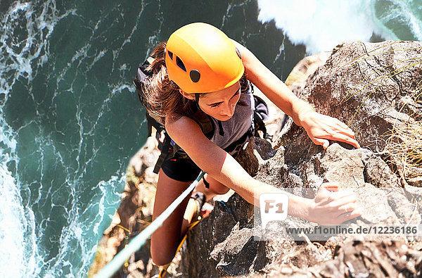 Fokussierte Klettererin  die vom Felsen über dem Meer hängt
