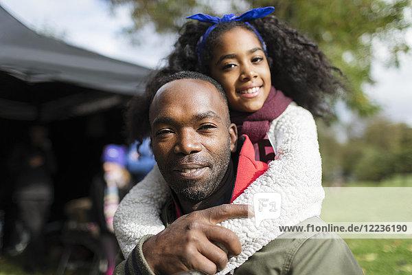 Portrait lächelnder Vater Huckepack-Tochter im Park