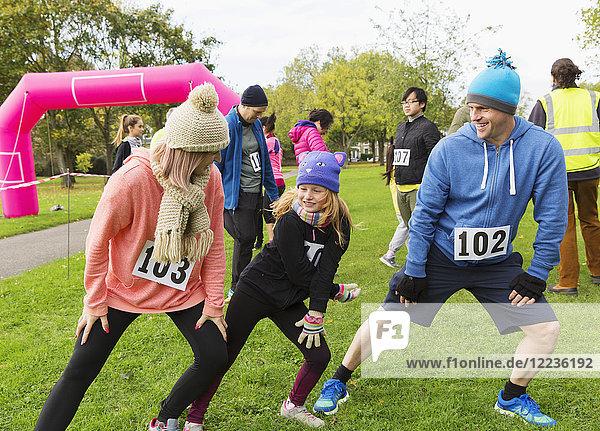 Familienläufer beim Stretching  Vorbereitung auf den Charity-Lauf im Park