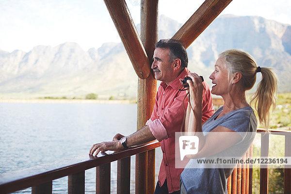 Paar mit Fernglas mit Seeblick vom Balkon aus