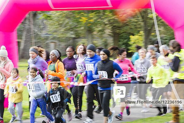 Läufer überqueren die Ziellinie beim Charity-Lauf im Park
