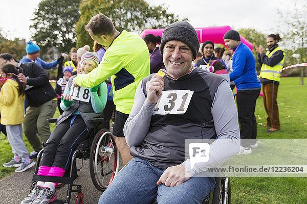 Portrait lächelnder  selbstbewusster Mann im Rollstuhl mit Medaille beim Charity-Rennen im Park