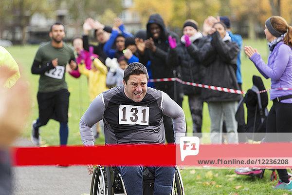 Entschlossener Mann im Rollstuhl  der sich dem Ziel des Benefizrennens im Park nähert.
