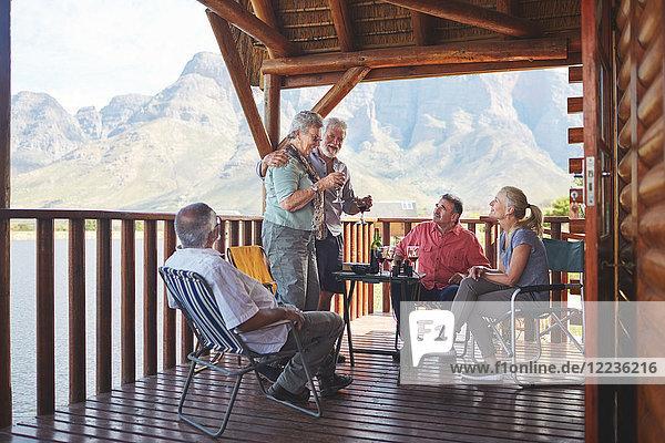 Aktives Seniorenpaar mit Weingläsern auf dem Balkon der Seehütte