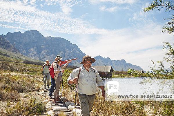 Aktive Seniorenfreunde beim Wandern und Genießen des sonnigen Seeblicks im Sommer