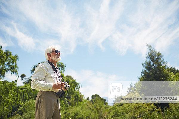 Neugieriger aktiver Senior mit Digitalkamera und Blick auf sonnige Bäume und Himmel
