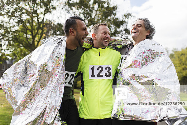 Fröhliche Marathonläufer in Thermodecke gehüllt