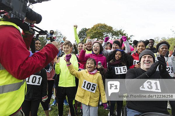Kameramann filmt jubelnde Läufer beim Benefizlauf