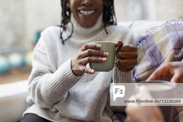 Frauen reden und trinken Tee auf dem Sofa