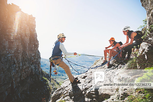 Rock climbers with ropes on sunny rock