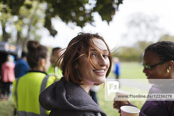 Portrait lächelnde Läuferin in Ruhe  Trinkwasser beim Benefizlauf im Park