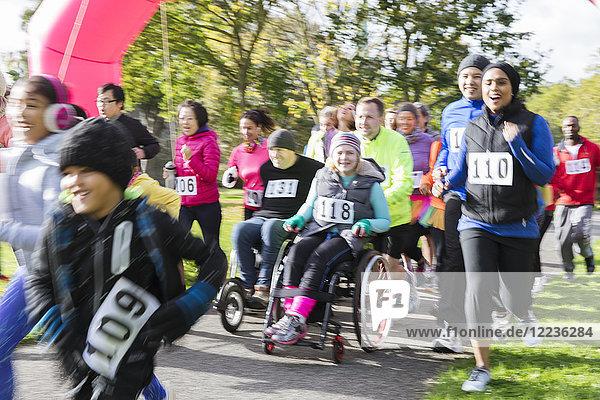 Läufer und Rollstuhlfahrer beim Benefizlauf im Park