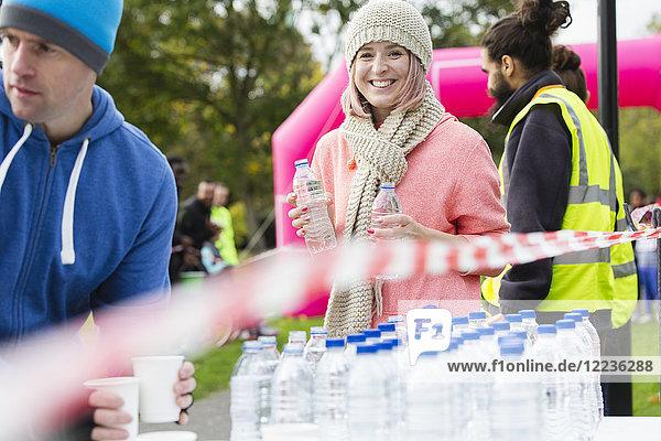 Porträt einer lächelnden Freiwilligen  die beim Spendenlauf Wasser austeilt