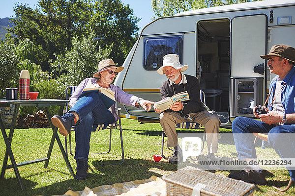 Aktive Seniorenfreunde beim Lesen vor dem Wohnmobil auf dem sonnigen Sommercampingplatz