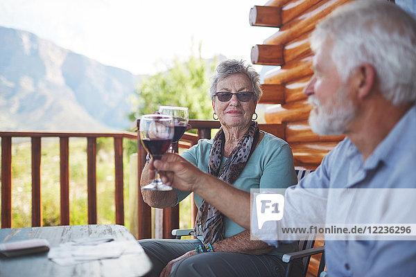 Aktives Seniorenpaar beim Rösten von Rotweingläsern auf dem Balkon