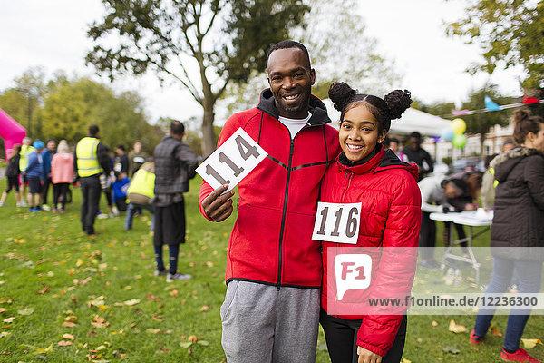 Porträt lächelnde  selbstbewusste Vater- und Tochterläufer mit Marathon-Lätzchen beim Charity-Lauf im Park
