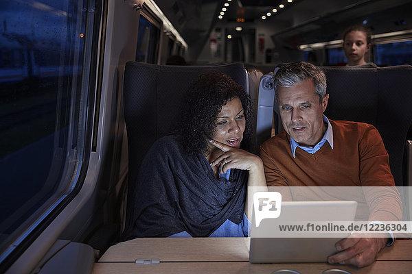 Paar mit digitalem Tablett im dunklen Personenzug bei Nacht