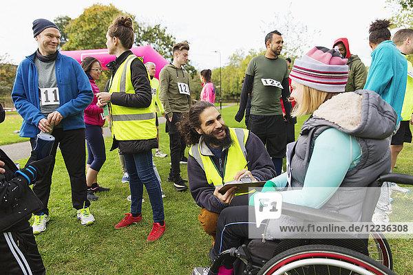 Frau im Rollstuhl beim Einchecken mit Freiwilliger beim Charity-Rennen im Park