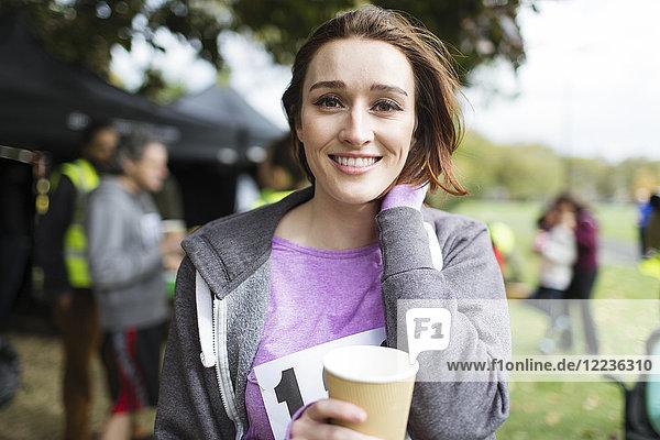 Portrait lächelnde Marathonläuferin Trinkwasser im Park