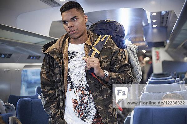 Junger Mann mit Rucksack beim Einsteigen in den Personenzug