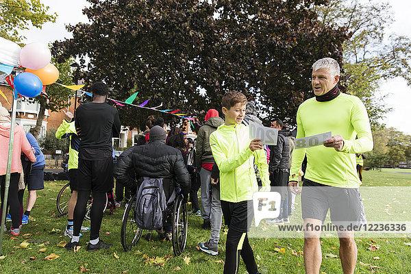 Vater und Sohn mit Marathon-Lätzchen beim Benefizlauf im Park