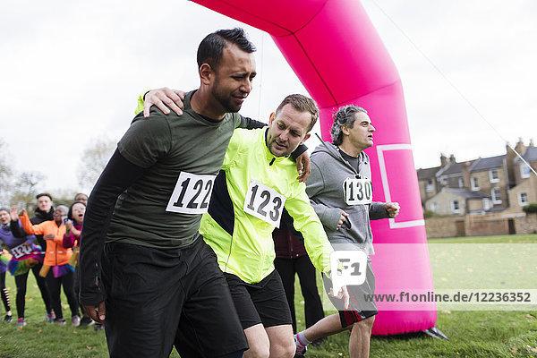 Mann hilft verletztem Läufer beim Überqueren der Ziellinie beim Benefizlauf