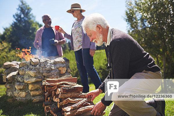Aktiver älterer Mann beim Stapeln von Brennholz