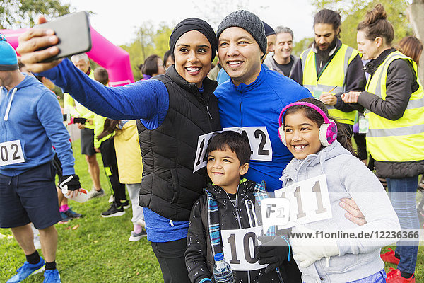 Familien-Wohltätigkeitsläufer  die Selfie mit Fotohandy mitnehmen.