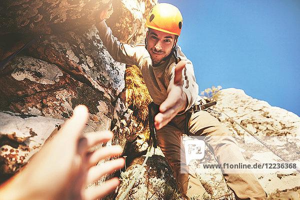 Persönliche Perspektive  die nach der Hand des Kletterers greift