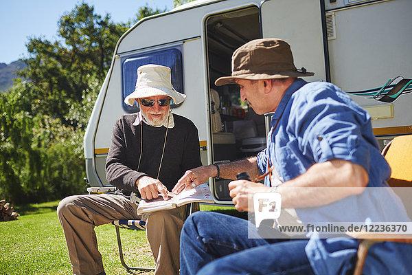 Seniorenfreunde schauen sich den Reiseführer vor dem Wohnmobil auf dem sonnigen Sommercampingplatz an.