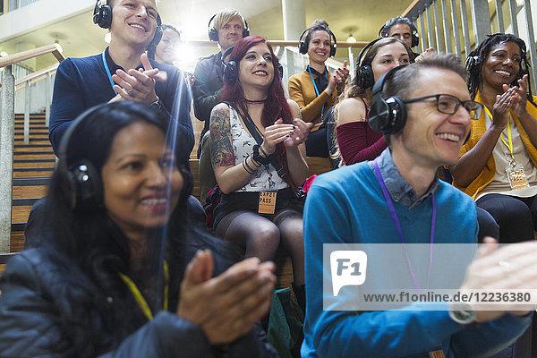 Lächelndes Publikum mit klatschenden Kopfhörern bei der Konferenz Lächelndes Publikum mit klatschenden Kopfhörern bei der Konferenz