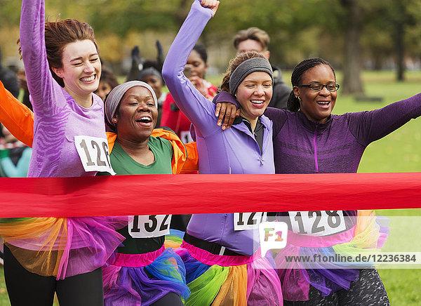 Läuferinnen im Tutuslauf  überqueren die Ziellinie des Wohltätigkeitslaufs