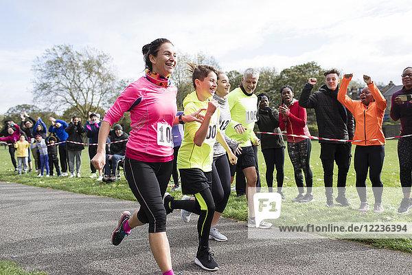 Enthusiastische Familienläufer beim Benefizlauf im Park