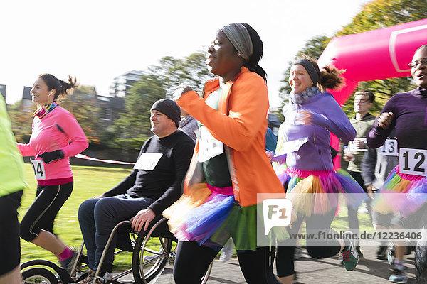 Läuferin in Tutu läuft in der Menge beim Charity-Lauf im sonnigen Park