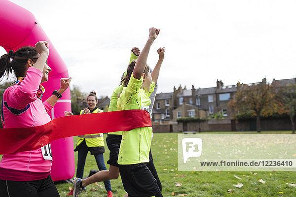 Enthusiastische Familienüberquerung beim Charity-Lauf im Park
