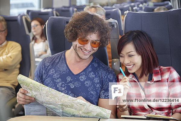Junges Paar beim Betrachten der Karte im Personenzug