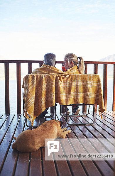 Gemütliches Paar und Hund auf dem Balkon
