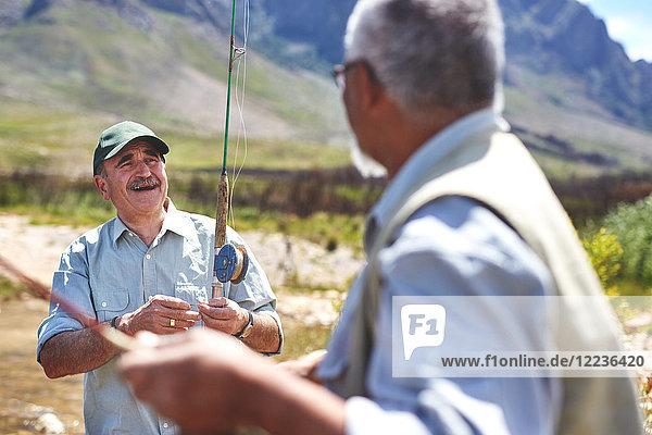Lächelnde aktive ältere Männer beim Fischen