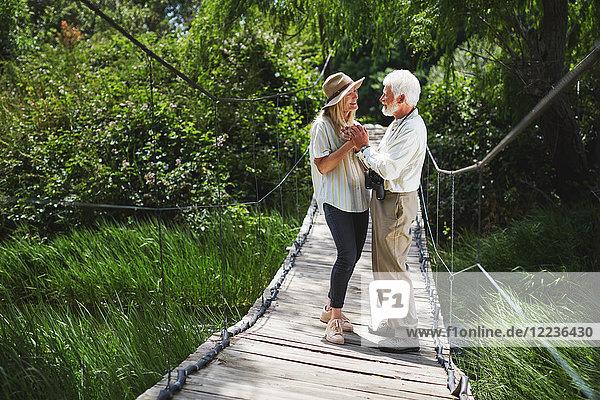 Romantisch aktives Seniorenpaar hält sich an der idyllischen Fußgängerbrücke fest.