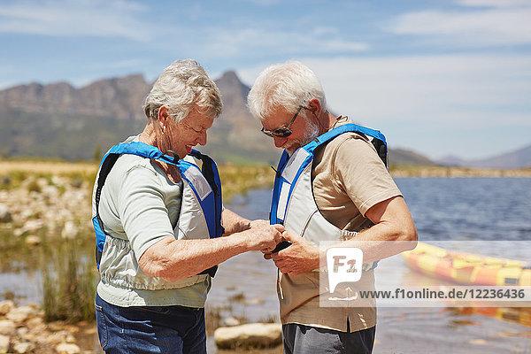 Aktives Seniorenpaar beim Anziehen von Schwimmwesten  Vorbereitung auf das Kajakfahren am sonnigen Sommerseeufer